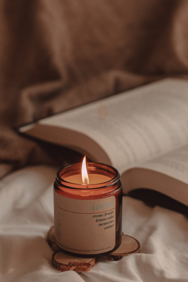 """a lit candle named """"addie"""" sits in front of an open book"""
