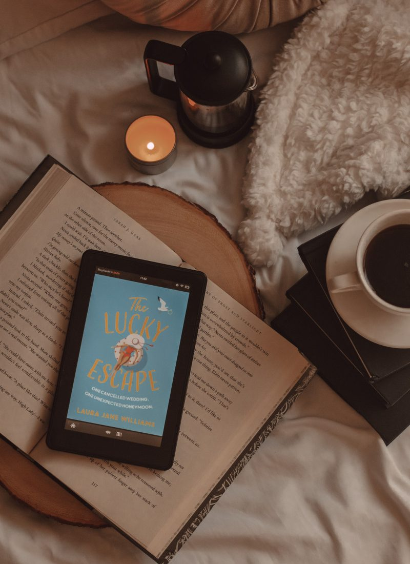 The Lucky Escape book cover shows on a Kindle screen as it lays on an open book next to a mug of coffee on top of a stack of books and a lit candle next to a french press