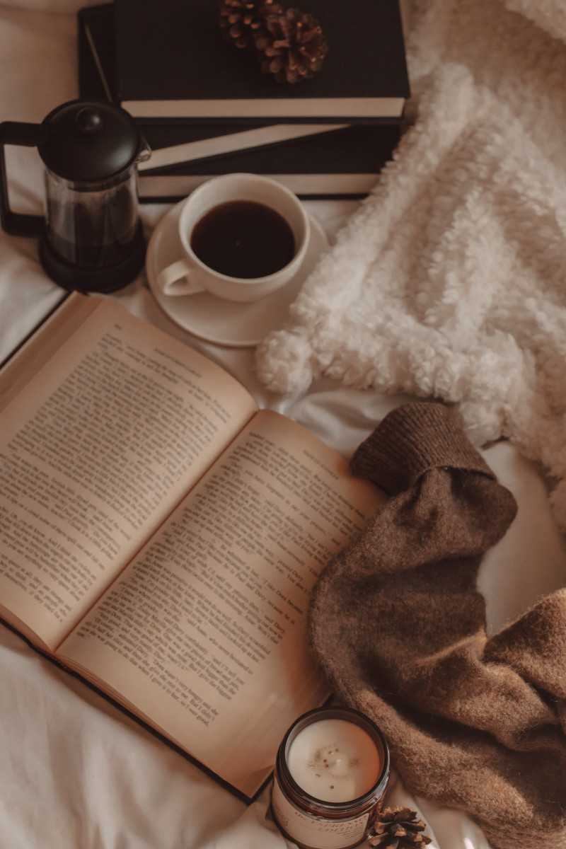 vintage book lies open with a mug of black coffee and french press next to a stack of black books and the arm of a sweater