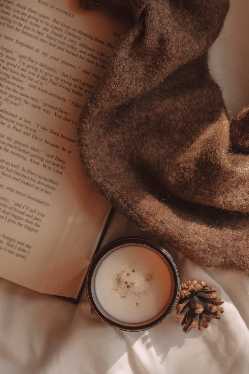 a candle with glitter on top sits next to a mini pinecone and pages of a book. a sweater lays across the books.