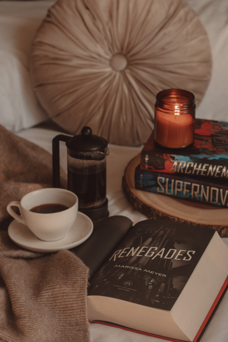 Renegades book open to title page next to a mug of coffee and French press. Archenemies and Supernova books stacked in the background with a lit candle on top