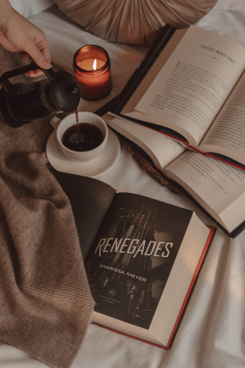 Renegades book title page open next to two other books stacked on top of one another and a hand pouring coffee into a mug