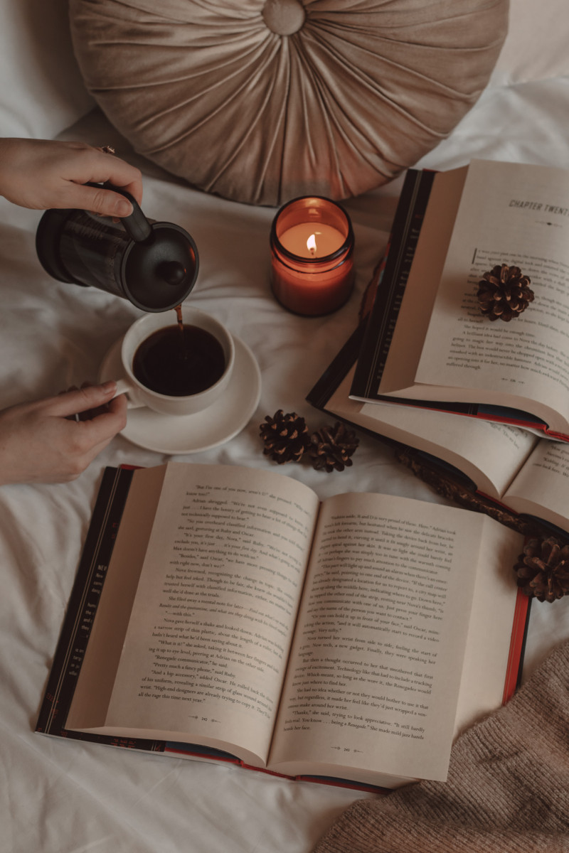 a book laying open next to a hand pouring coffee into a mug, a lit candle, and two books laying open on top of one another