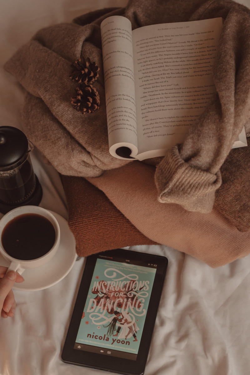 Instructions for Dancing book cover visible on e-reader with a cup of coffee next to a french press. A book is folded open on top of a pile of sweaters.