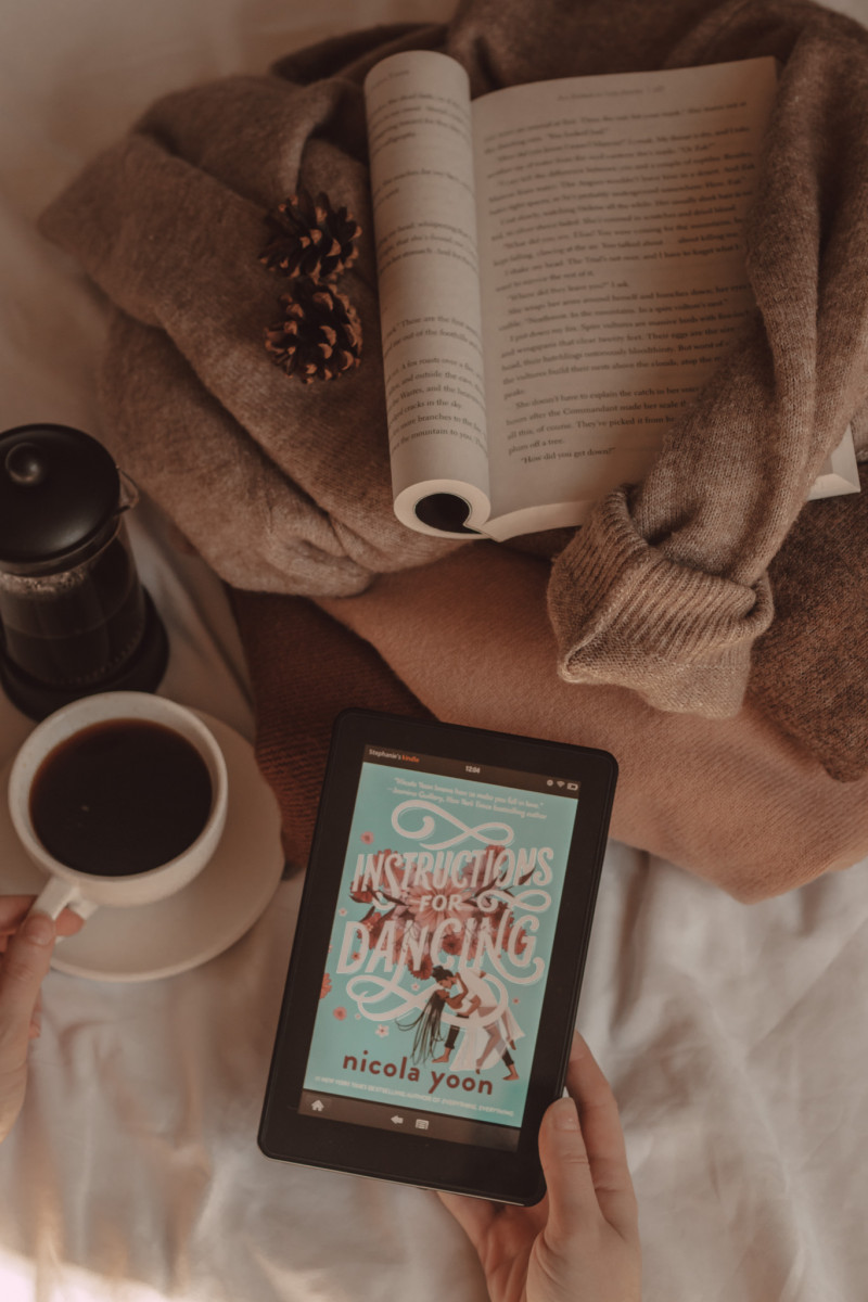 An e-reader shows the cover of Instructions for Dancing by Nicola Yoon while a book lays on top of a stack of sweaters and a hand holds a mug of coffee next to a French press.