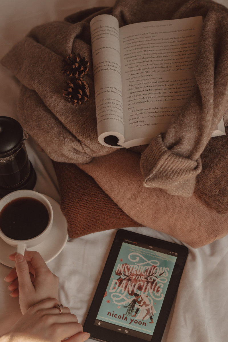 A hand holds a mug of black coffee next to a French press and a Kindle with the cover of Instructions for Dancing visible on the screen. Next to them, a stack of sweaters has a paperback book folded open on top of it.