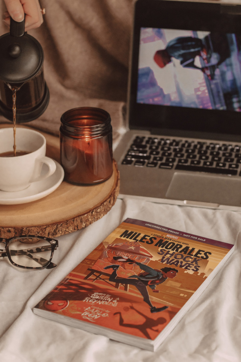 graphic novel of miles morales sits cover-up in the foreground next to a pair of glasses, a coffee mug, and a candle. laptop open to reveal screen in the background