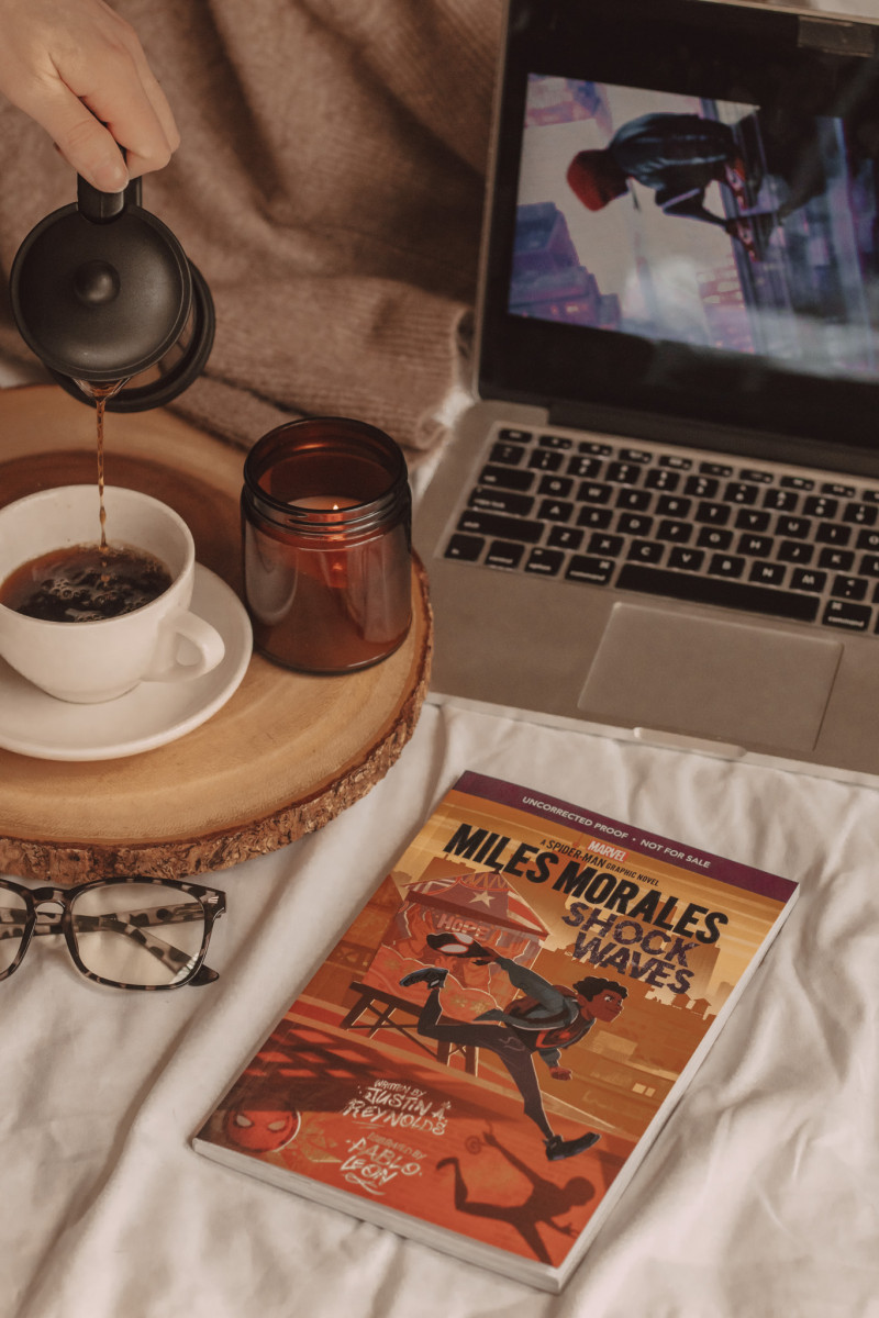 miles morales graphic novel sits next to a pair of glasses and a laptop while a hand pours coffee into a mug next to a candle