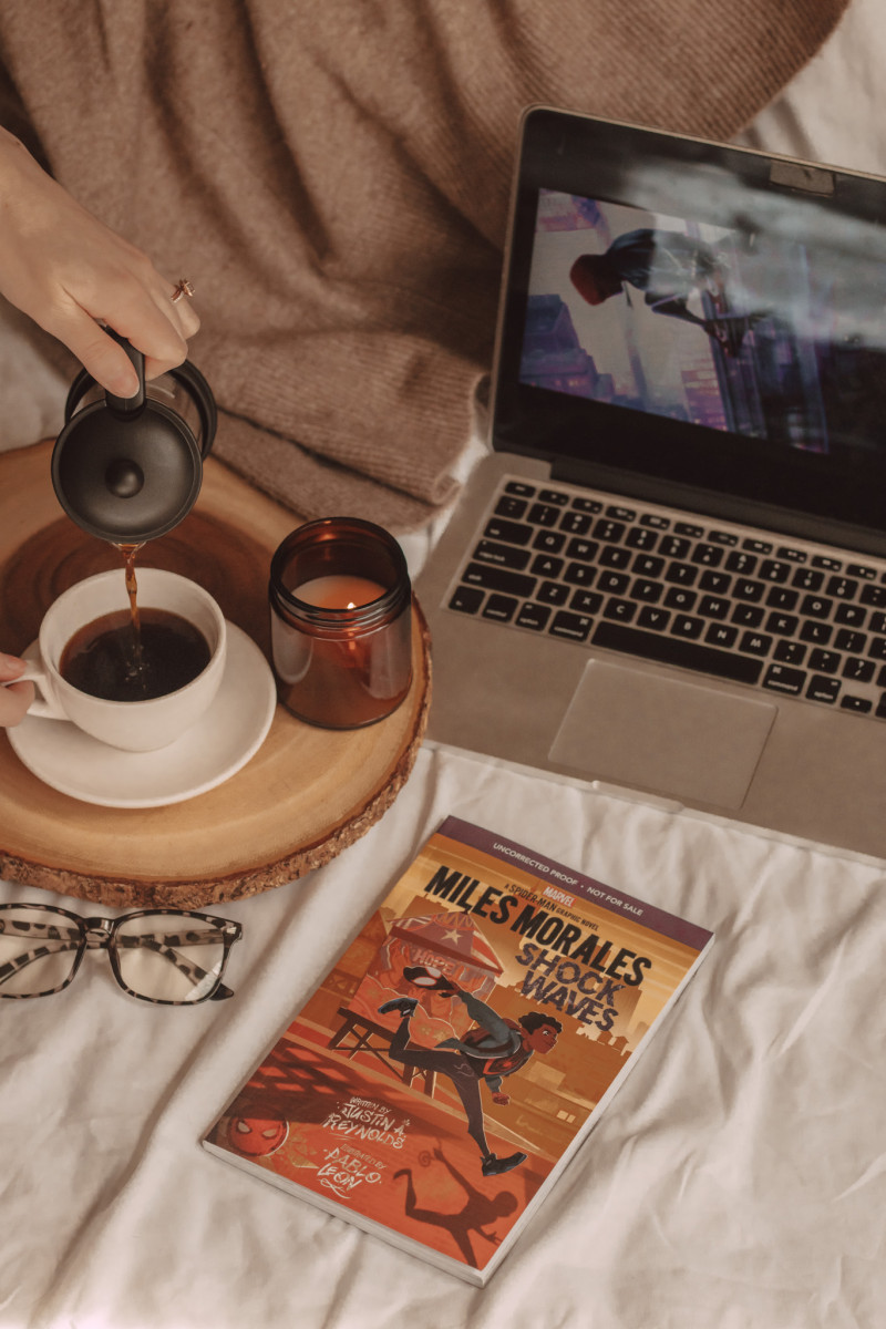 miles morales shock waves graphic novel laying next to a wooden board where a hand pours coffee. laptop in the background