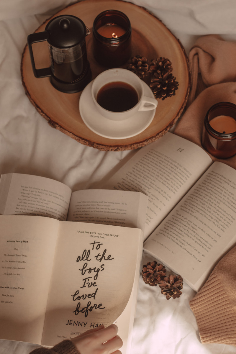to all the boys i've loved before book open to the title page and laying on top of two other books next to a mug of coffee and a french press