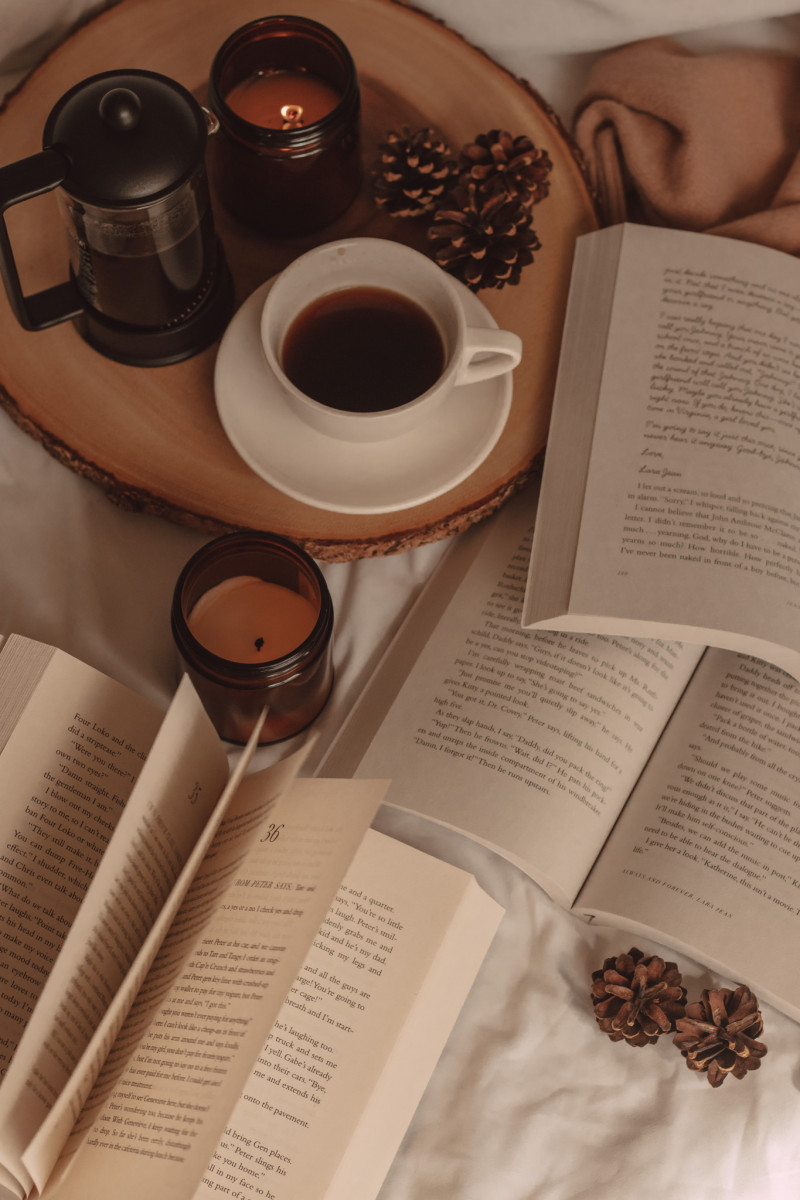 a book with the pages flipping next to two open books, a mug of coffee, and a candle