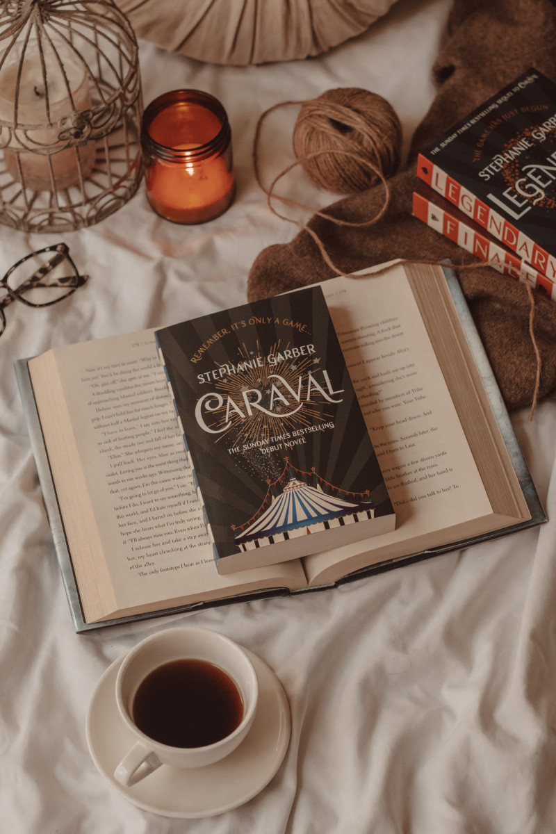 Caraval book lying on top of an open book next to a mug of black coffee and lit candle