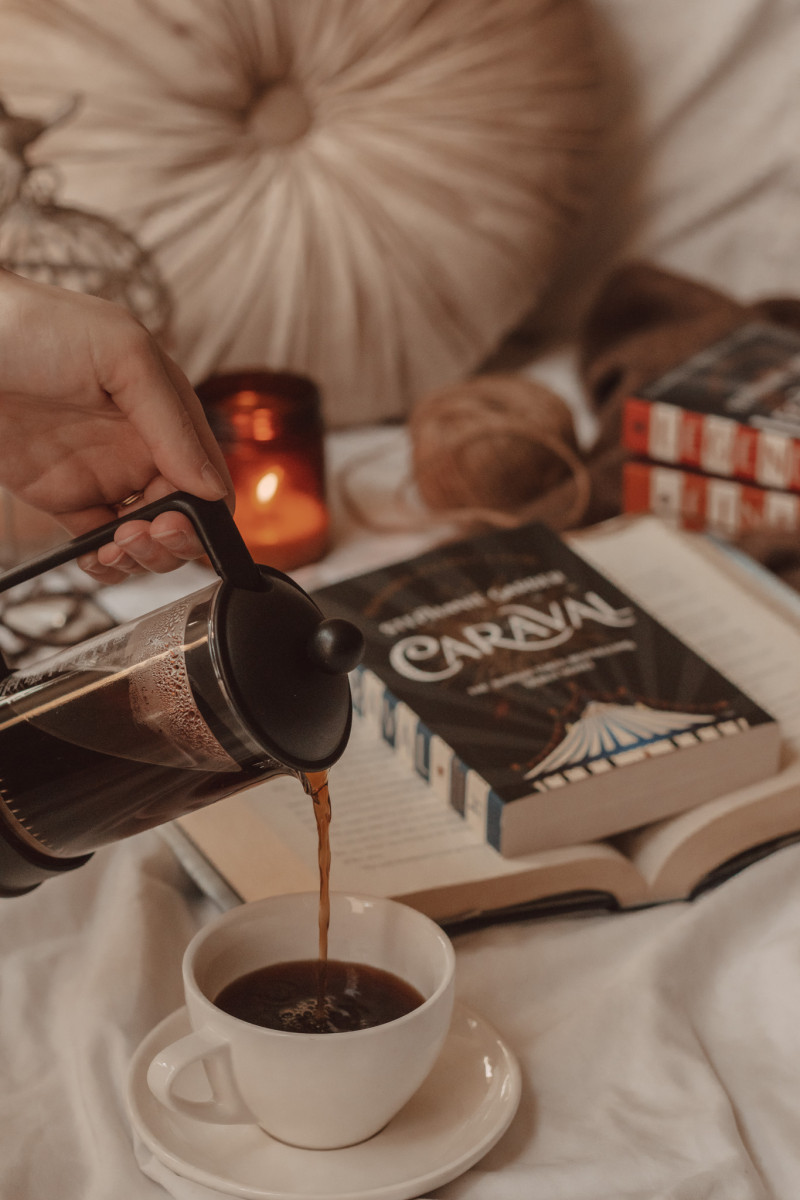 black coffee poured from a french press into a mug in the foreground with Caraval in the background laying on an open book with a lit candle burning next to it