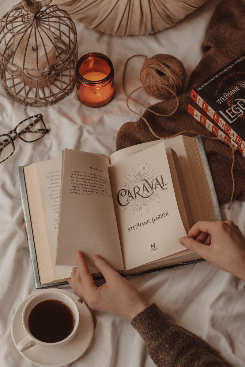 hands flipping through the pages of Caraval with a mug of coffee and burning candle nearby