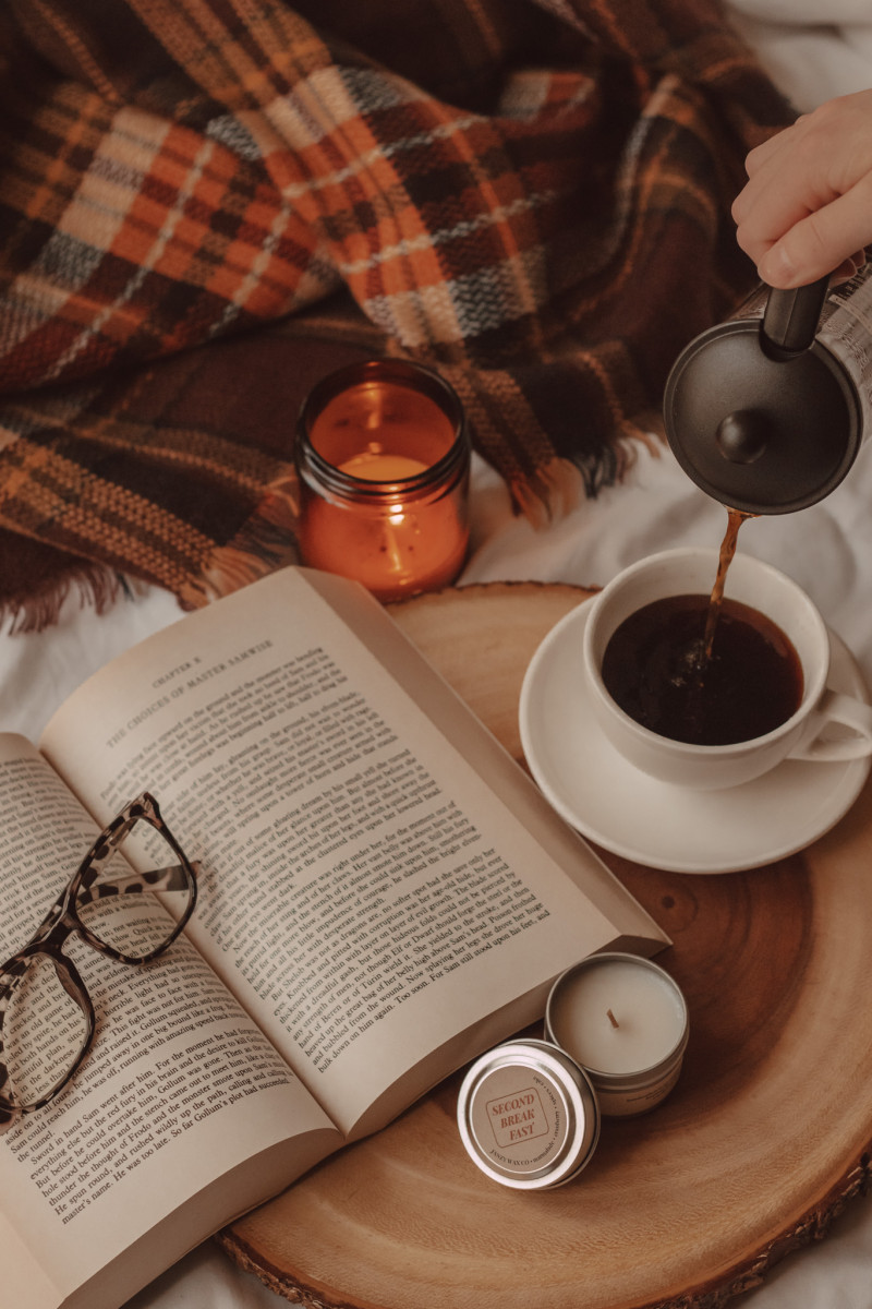 a hand pours black coffee into a mug next to an open book with glasses laying on top. a lit candle in a jar is in the background with a plaid scarf and a small, unlit candle tin is in the front on a wooden cake tray.