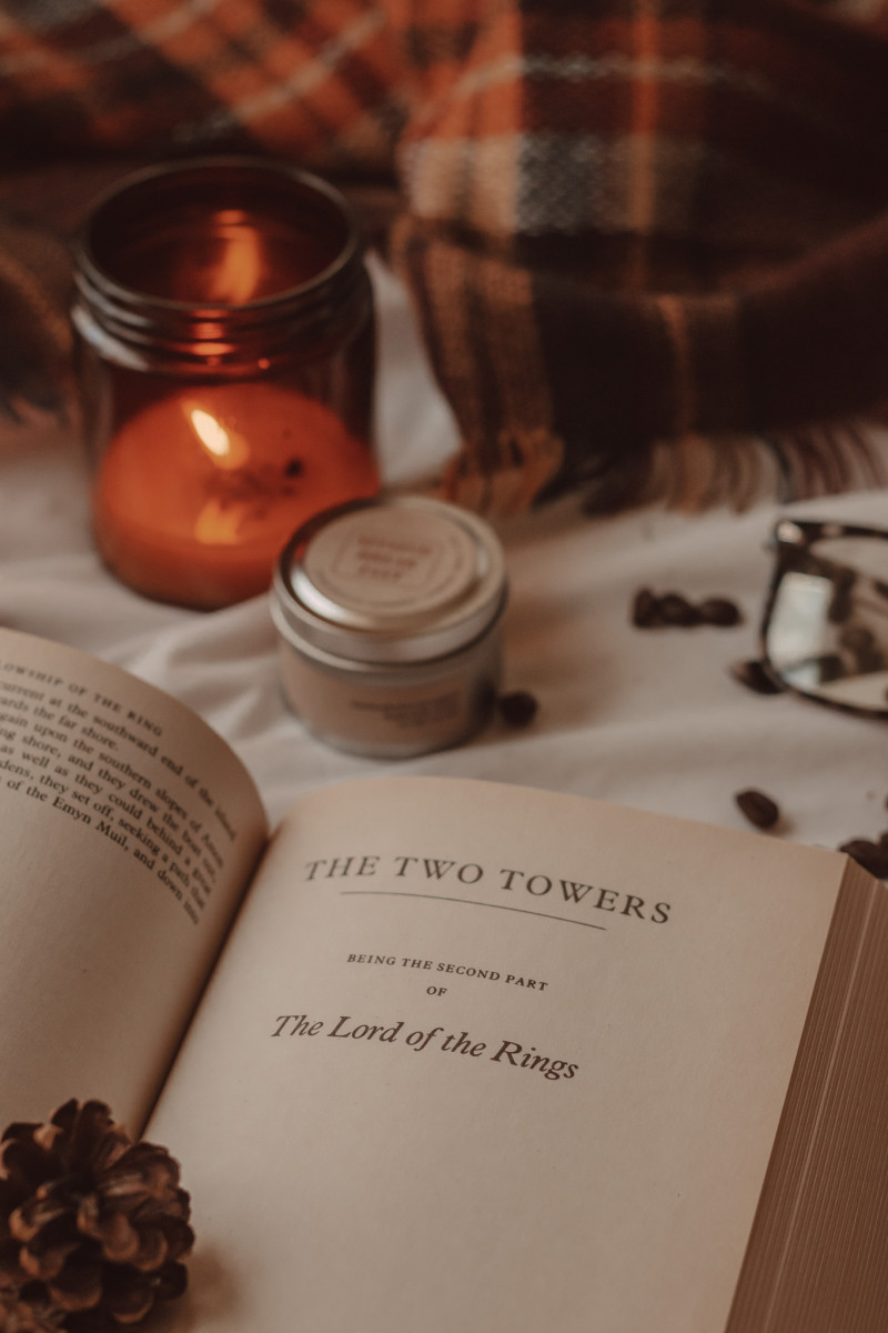 a close-up shot of the title page for the two towers. a small pinecone sits on top and a candle burns in the background next to a small tin and a pair of glasses.