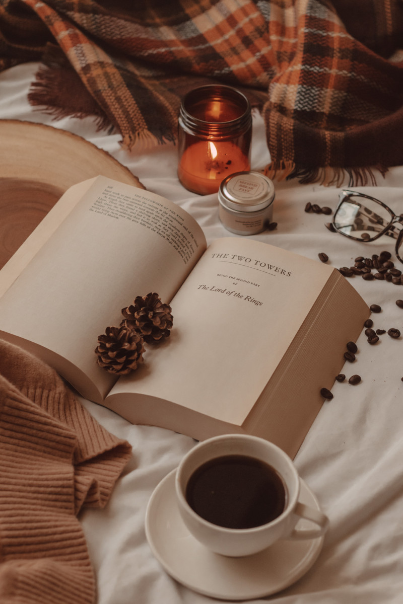 a book lies open with two small pinecones lying in the center. a mug of coffee sits on a saucer in the foreground. behind the book are two candles, coffee beans, and a pair of glasses.