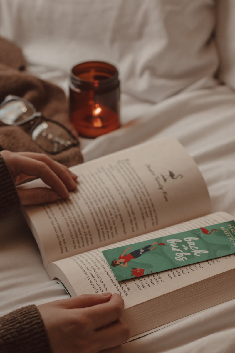 bookmark lays on an open book while a hand holds the book open and a candle burns in the background