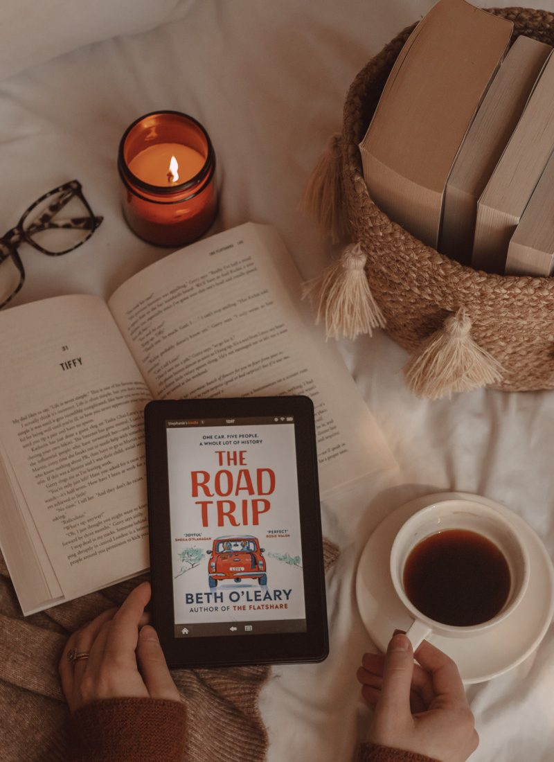 hands grip a mug of coffee and e-reader with The Road Trip book cover on it. beneath lies an open book and next to it are a basket of books and a lit candle