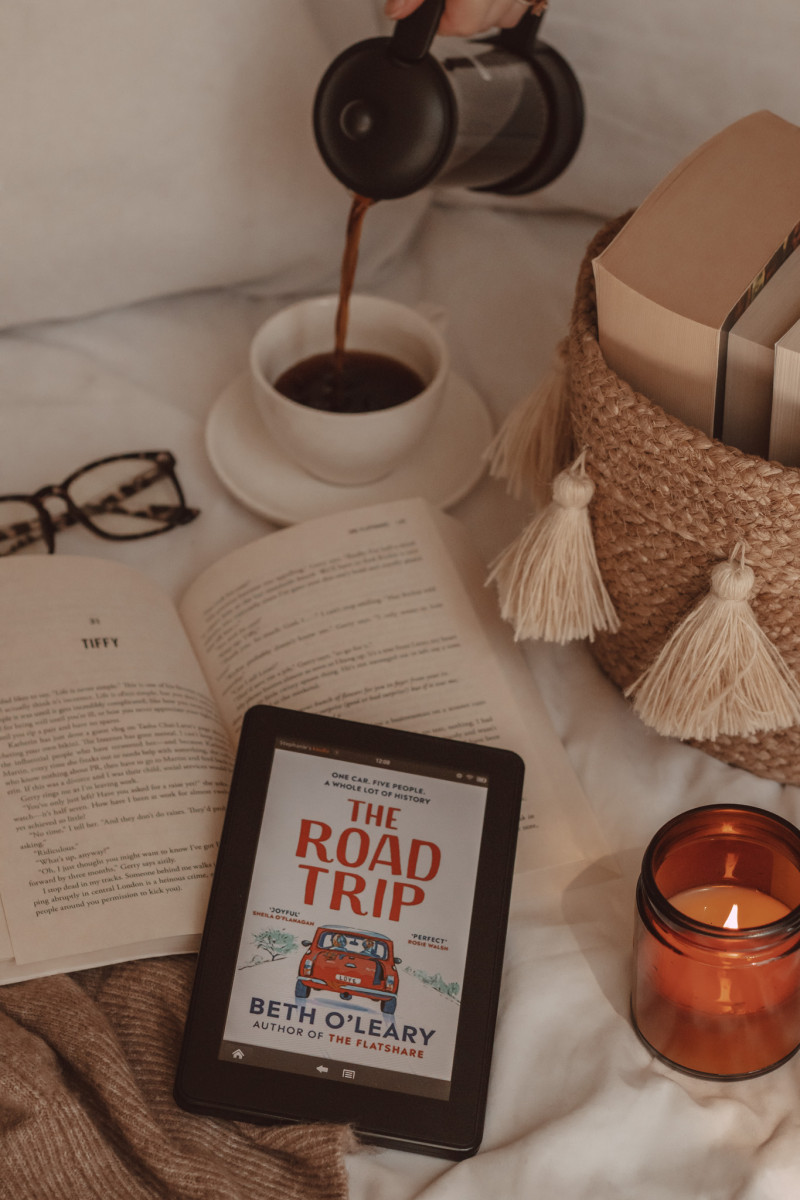 an e-reader is in the foreground with The Road Trip book cover on the screen. next to it is a lit candle and behind it is a basket of books and a hand pouring black coffee into a mug