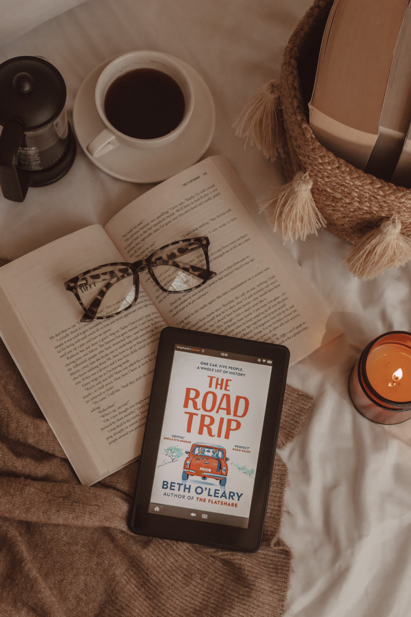 from above you see a kindle with The Road Trip book cover on it. it lies on an open book with a pair of glasses. next to it is a lit candle, a mug of black coffee, and a basket of books