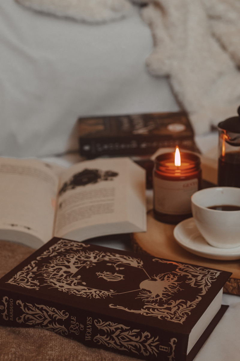 rule of wolves book without dust jacket next to open book, lit candle, and coffee mug