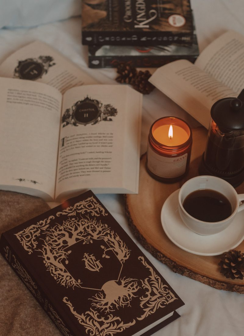 ornate embossed book sits next to two open books, a lit candle, and a mug of black coffee
