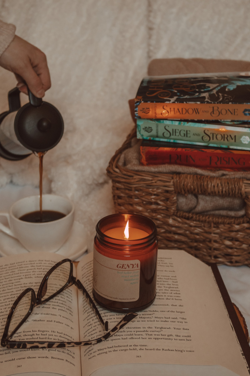 lit candle and pair of glasses sitting on an open book while a hand pours coffee into a mug in the background and the shadow and bone trilogy is stacked on a basket