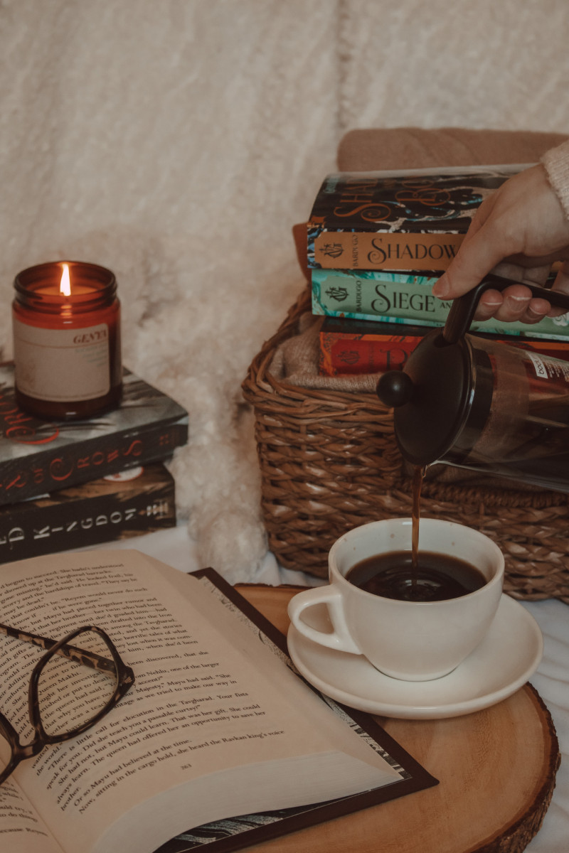 hand pouring coffee into a mug next to an open book with a lit candle on top of two books and three books stacked on a basket in the background