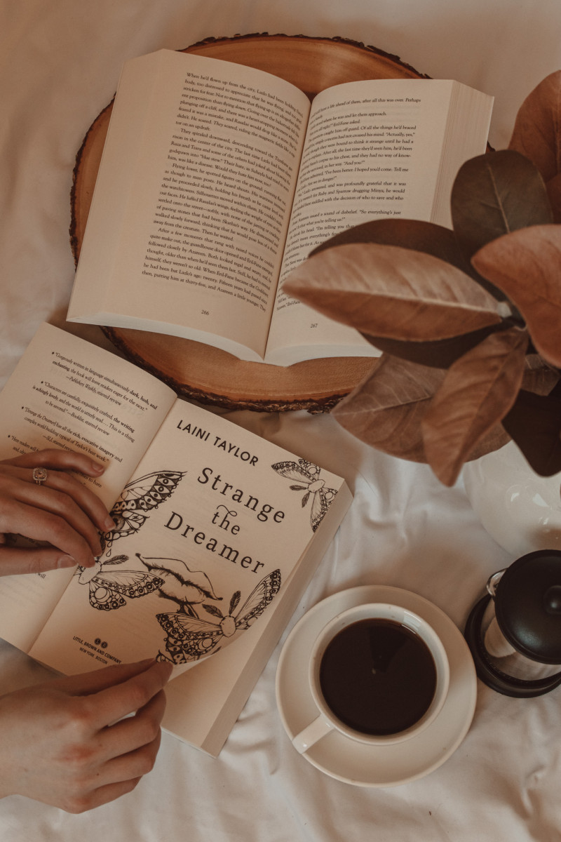 strange the dreamer title page next to an open book on a wooden tray with a mug of black coffee next to it
