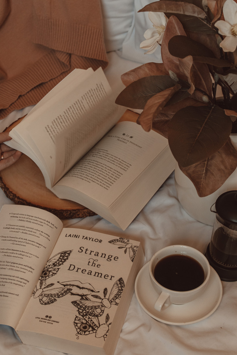 strange the dreamer opened to the title page next to a mug of black coffee and a book with the pages being flipped open