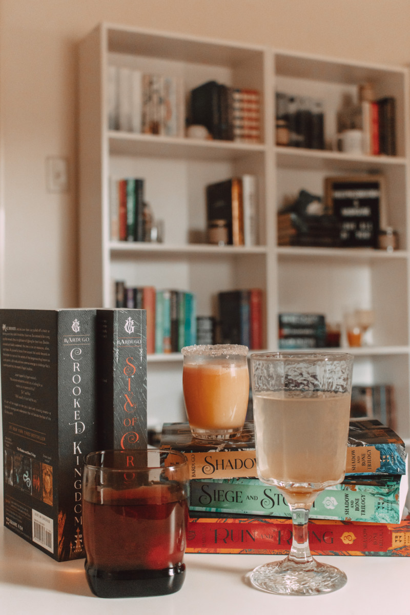 three drinks stand beside and on top of stacked books with bookshelves in the background