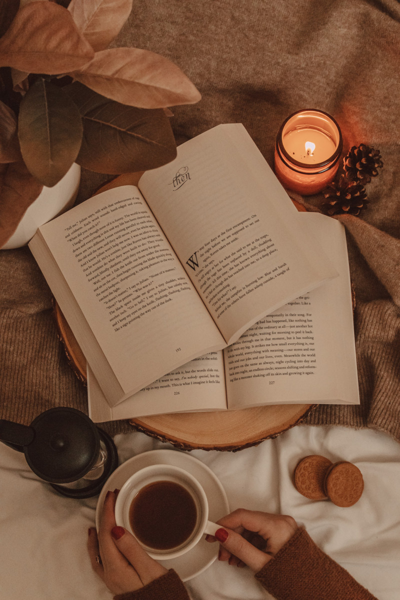 two open books laying atop each other with a burning candle and a mug of black coffee