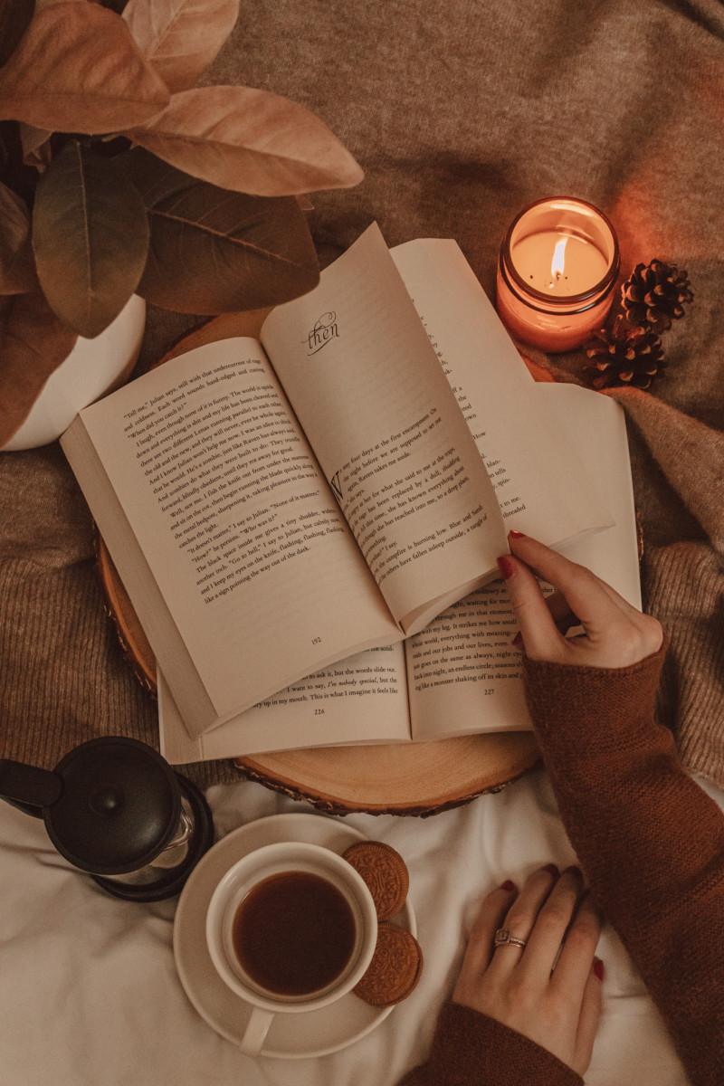 a hand flips the page of an open book on top of another open book. a burning candle and a mug of coffee sit nearby