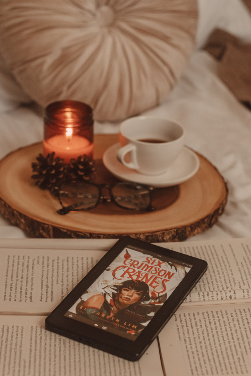 kindle with six crimson cranes book cover visible laying on top of several open books with a wooden board in the background, holding a mug and a lit candle