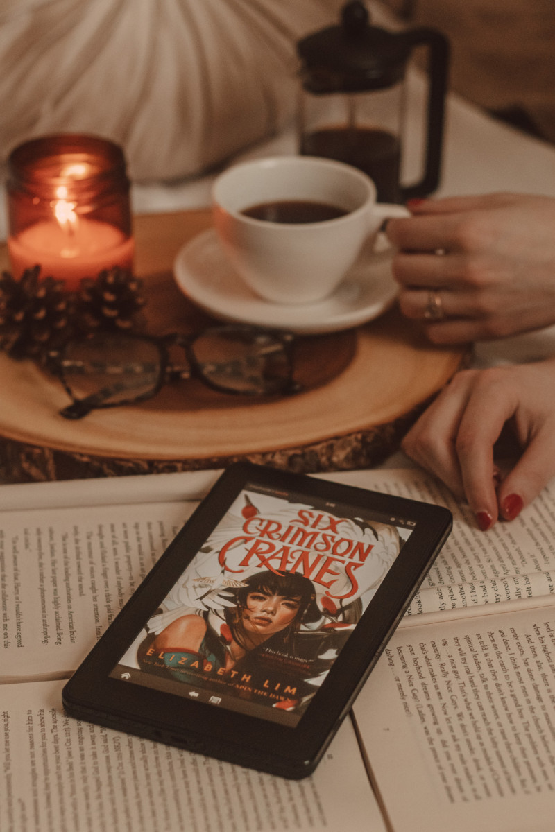 hands hold a mug of coffee next to a lit candle in the background while an ereader sits on top of open books with six crimson cranes cover visible on the screen.