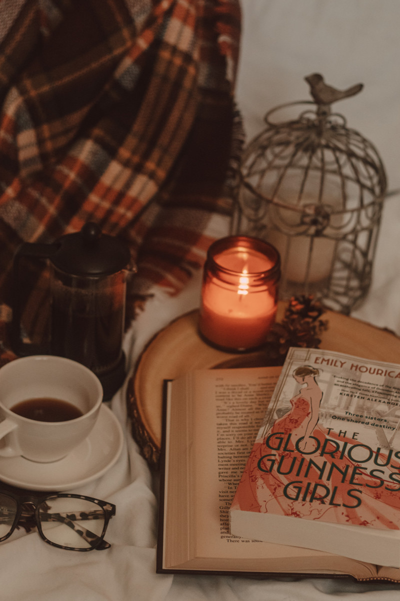 The Glorious Guinness Girls book sits atop an open book on a wooden cake tray next to a lit candle and mug of coffee