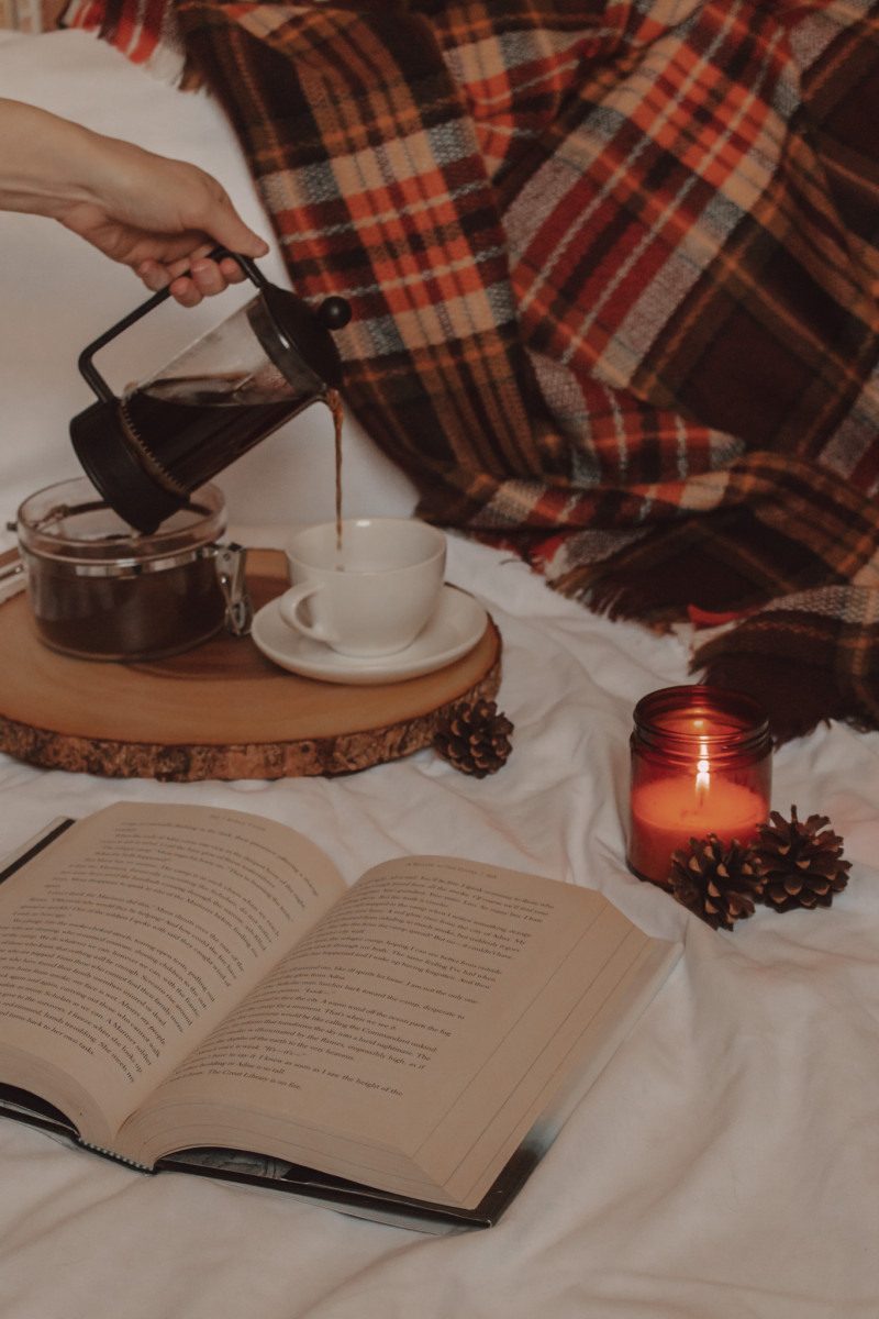 in the foreground is an open book and behind it a candle is burning next to two pinecones. the background has a hand pouring coffee into a mug next to a plaid blanket