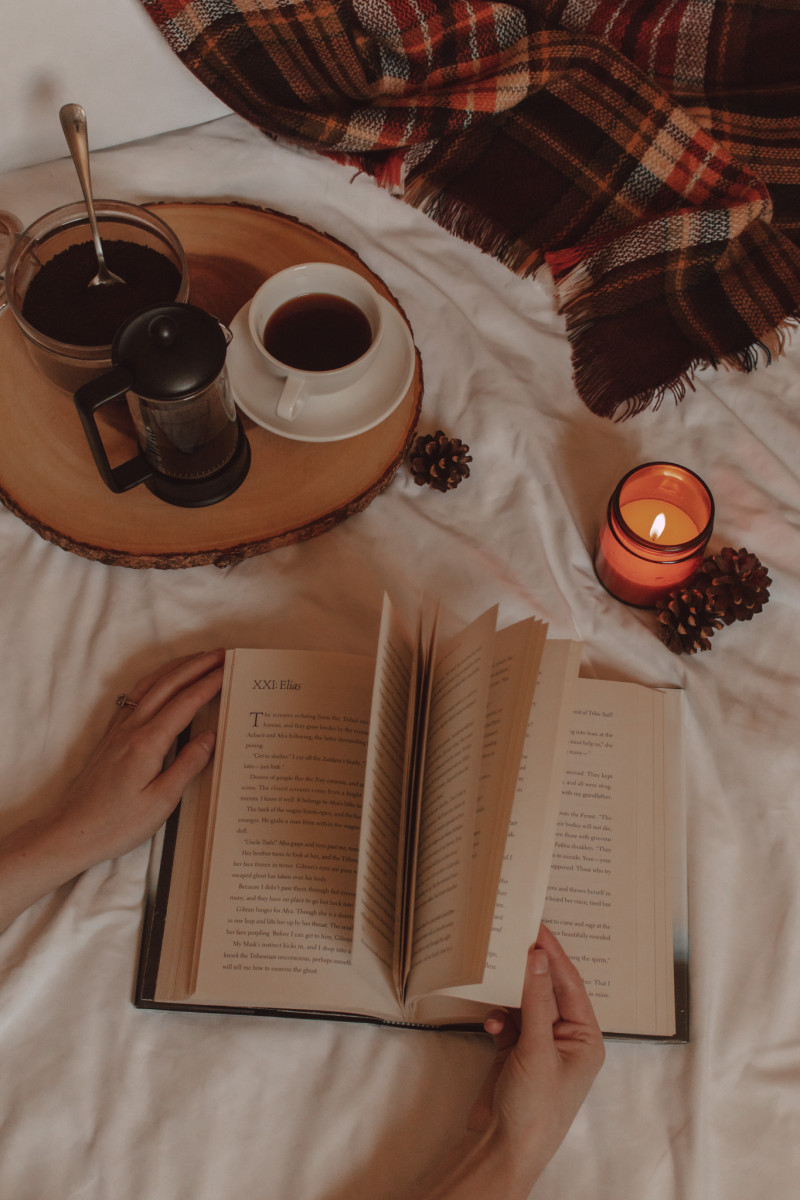hands flip the pages of a book next to a burning candle and a mug of coffee