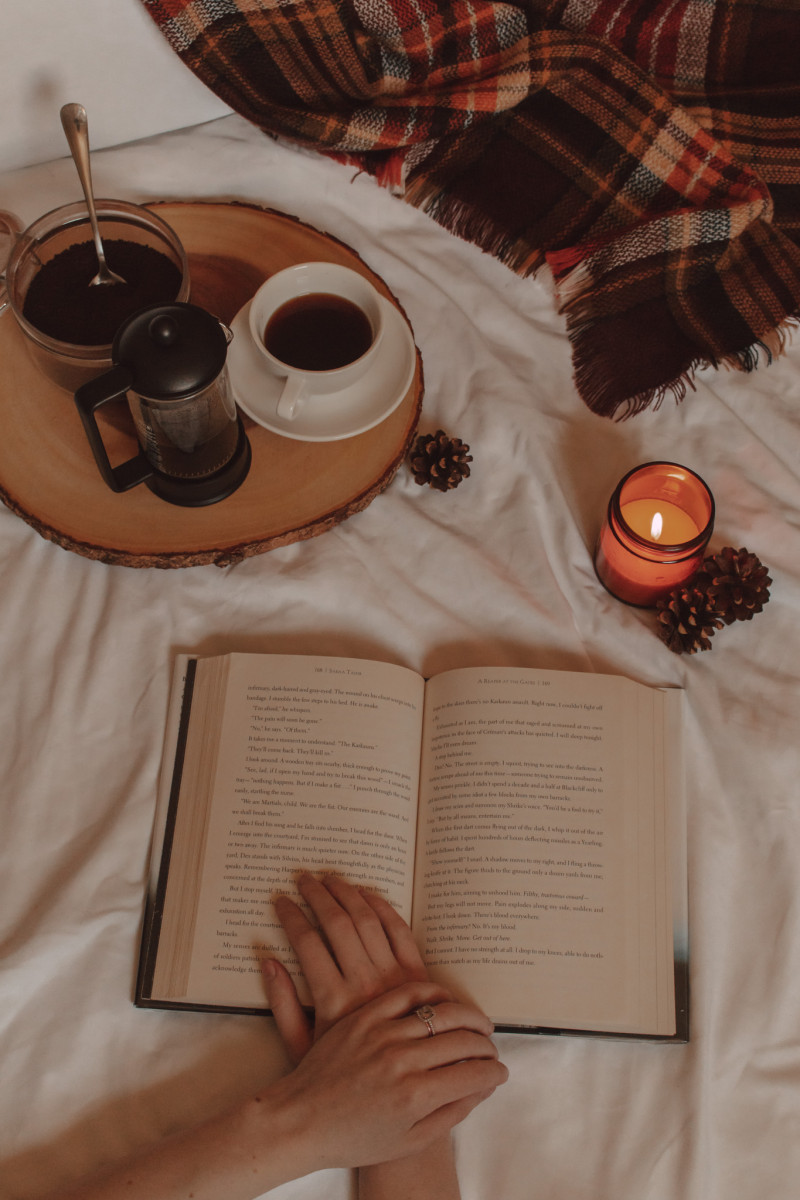 an open book with a hand on top next to a lit candle and cup of black coffee